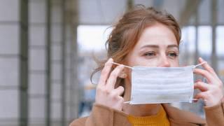 Kobieta zakłada maseczkę